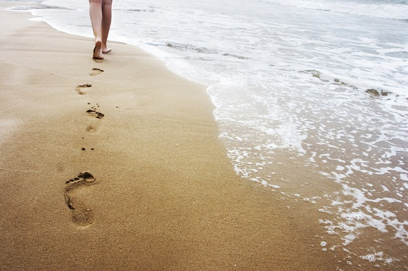 A young woman walking on the sand, Burn More Calories By Running On Sand