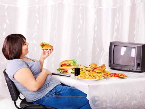 woman-watching-tv-and eating unhealthy
